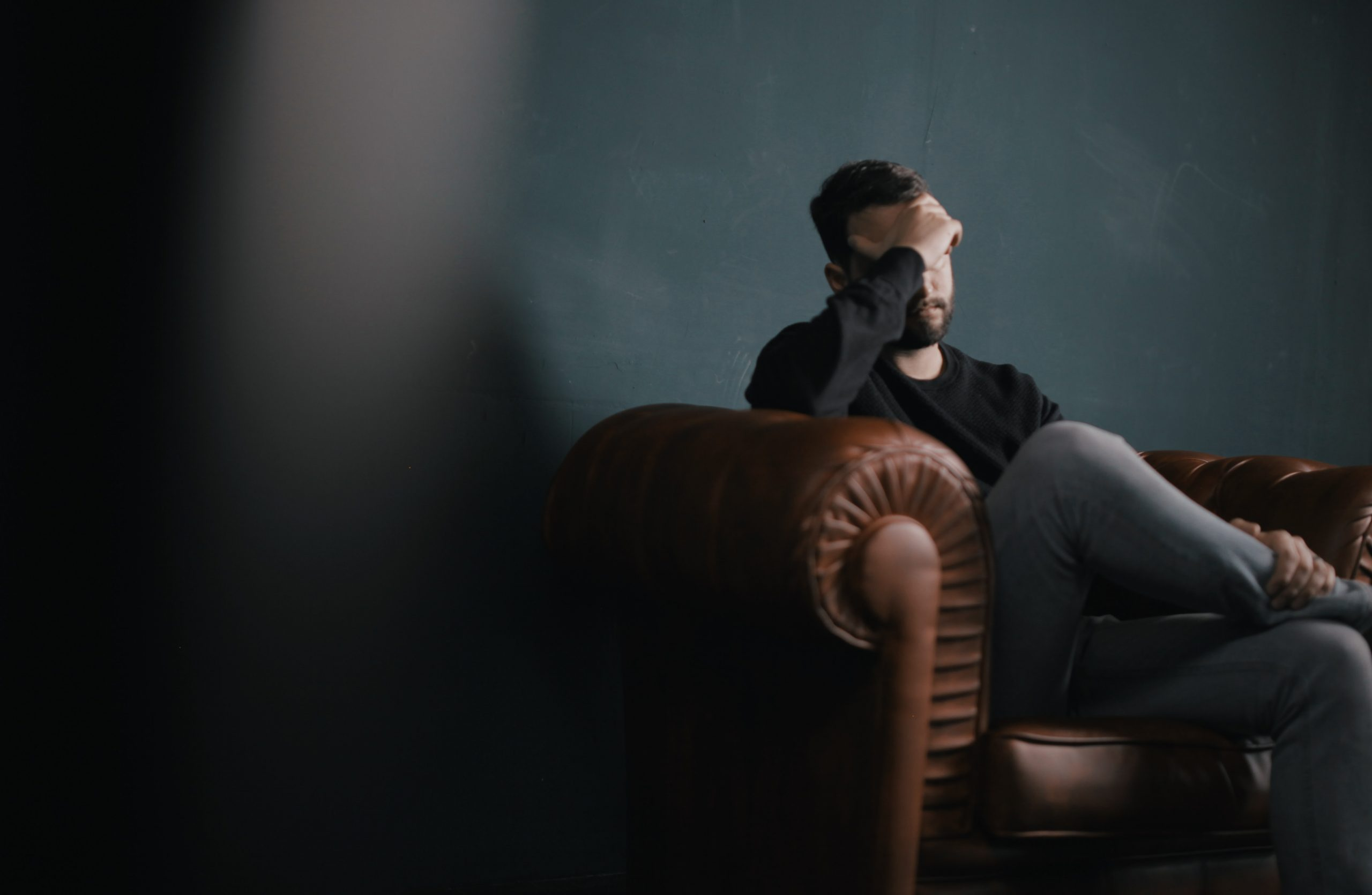 Guy on couch with head in his hands