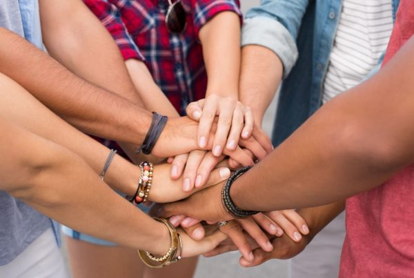 Multi-racial friends stacking hands together